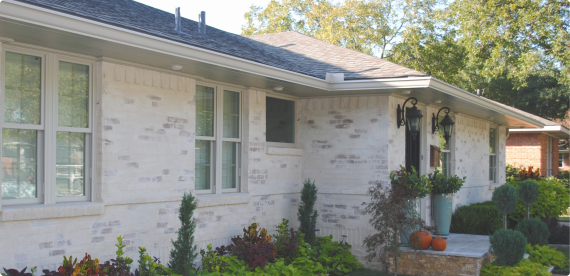 A brick home with a newly installed talbert gutter system